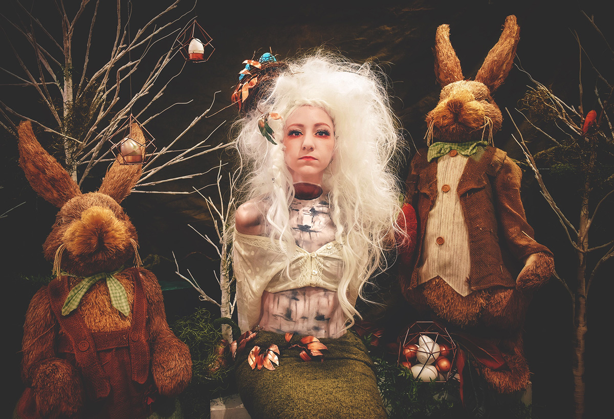 A woman with birch tree painting body and floating head with two bunny rabbits next to her